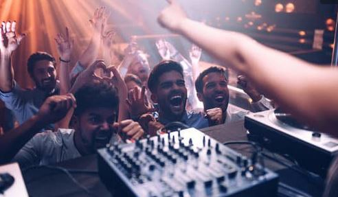 a couple of guys in front of a DJ booth, very enthusiastic.
