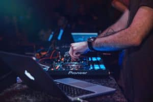 image of DJ performing behind a dj booth with a laptop.